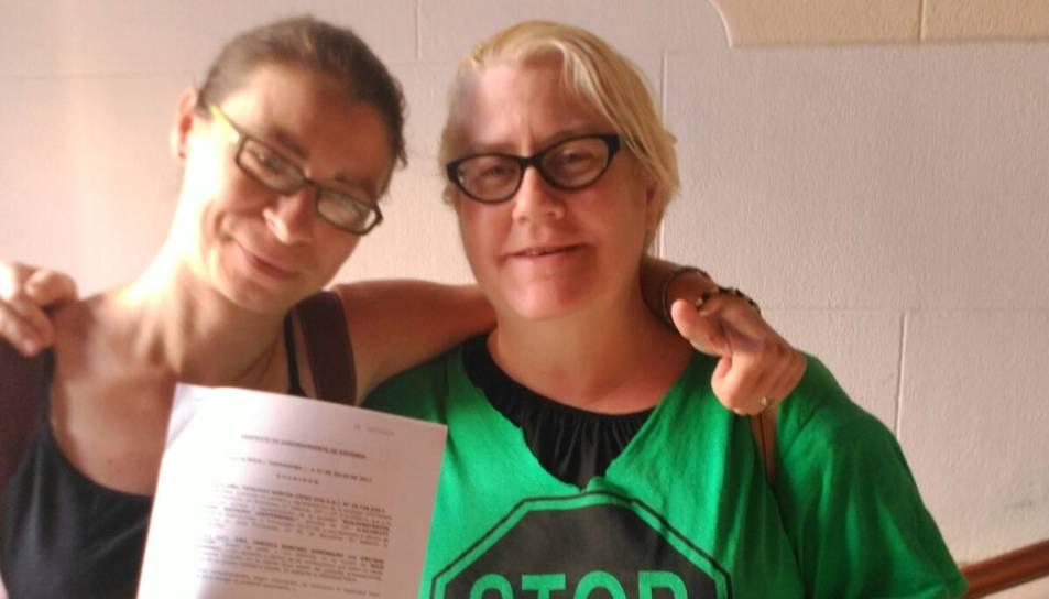 La nova inquilina i l'activista de la PAH mostren el contracte.