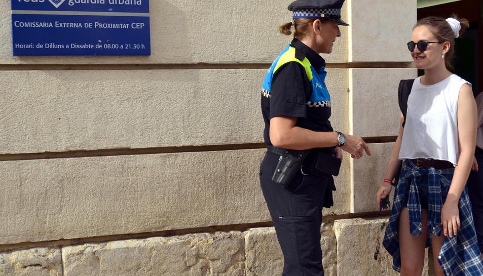 Una agent de la Guàrdia Urbana de Reus atén una ciutadana a les portes d'una de les CEP de la ciutat. Imatge de l'1 d'agost de 2017 (horitzontal)