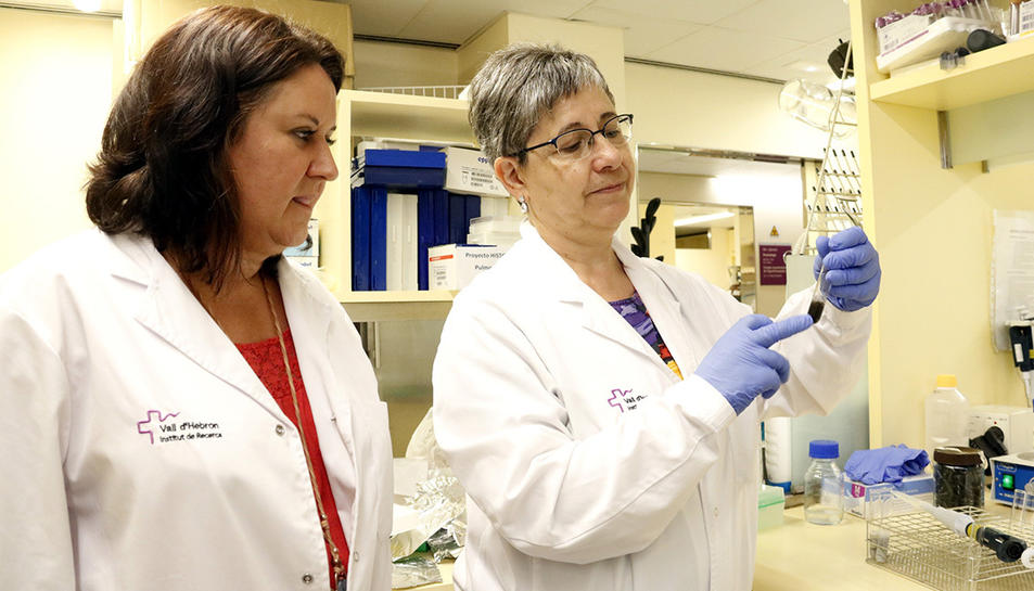 La cap del grup de recerca de Pneumologia, la doctora Maria Jesús Cruz (esquerra), i la doctora María Dolors Untoria, observen una proveta amb partícules de l'aire de Barcelona al seu laboratori del VHIR.