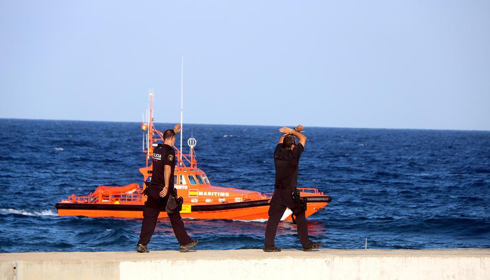 Dos agents dels Mossos d'Esquadra indicant que s'aturi el dispositiu de recerca del banyista desaparegut a la platja del Miracle de Tarragona, amb una embarcació de Salvament Marítim al fons.