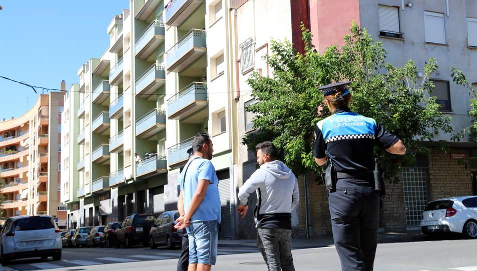 Agents de la Guàrdia Urbana de Reus, en primer terme, conversant amb gitanos que han ocupat un dels pisos, i dalt d'un balcó dels habitatges ocupats, una dona observant-los.