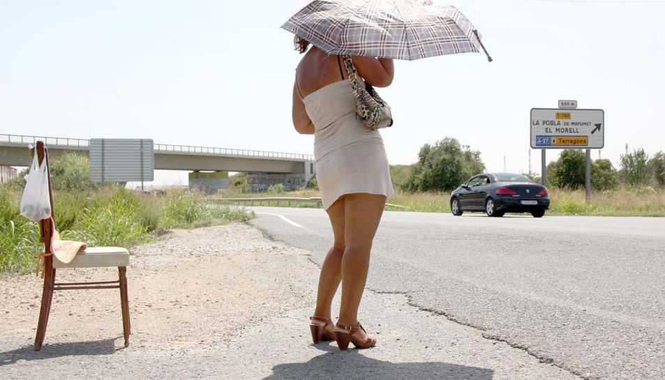Una noia prostituta a l'N-240 entre Tarragona i Valls, tapant-se amb un paraigua sota un sol de justícia.
