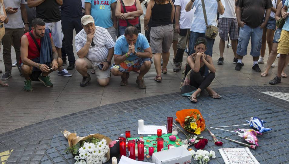 Flors i espelmes dipositades aquest divendres davant el mosaic de Miró a les Rambles de Barcelona.