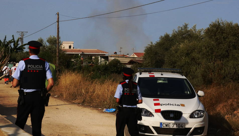 Dos agents dels Mossos d'Esquadra d'esquena, amb una columna de fum al davant durant una detonació controlada a Alcanar.