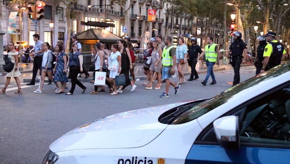 Agents acompanyant ciutadans per allunyar-se del centre de Barcelona dijous a la tarda.