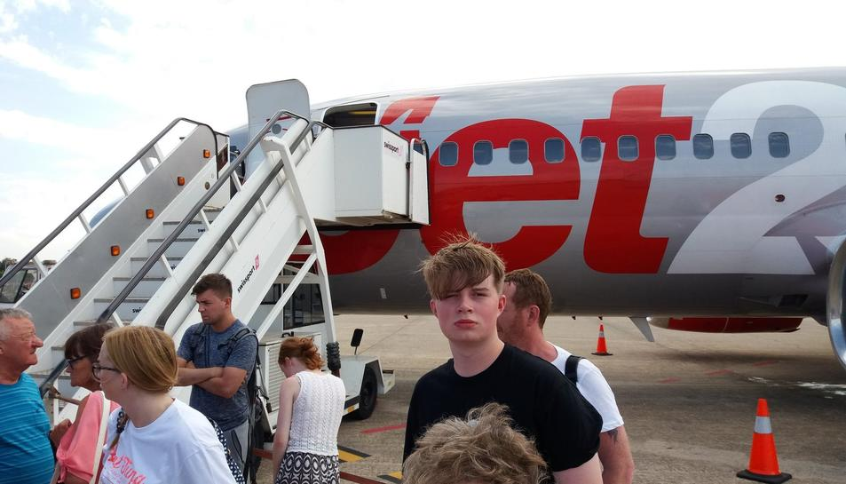 Passatgers de l'avió afectat esperen informació a la pista.