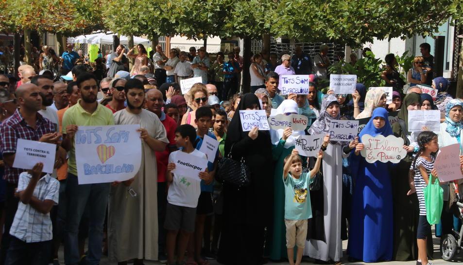 Pla obert de diversos manifestants musulmans a Valls, amb pancartes, en la concentració a Valls. Imatge del 26 d'agost de 2017