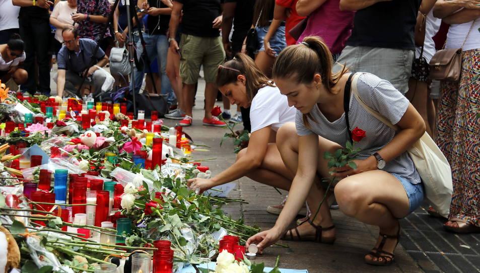 Dues noies encenen espelmes a les Rambles, en un dels punts improvisats de record a les víctimes dels atemptats, en una imatge d'arxiu.