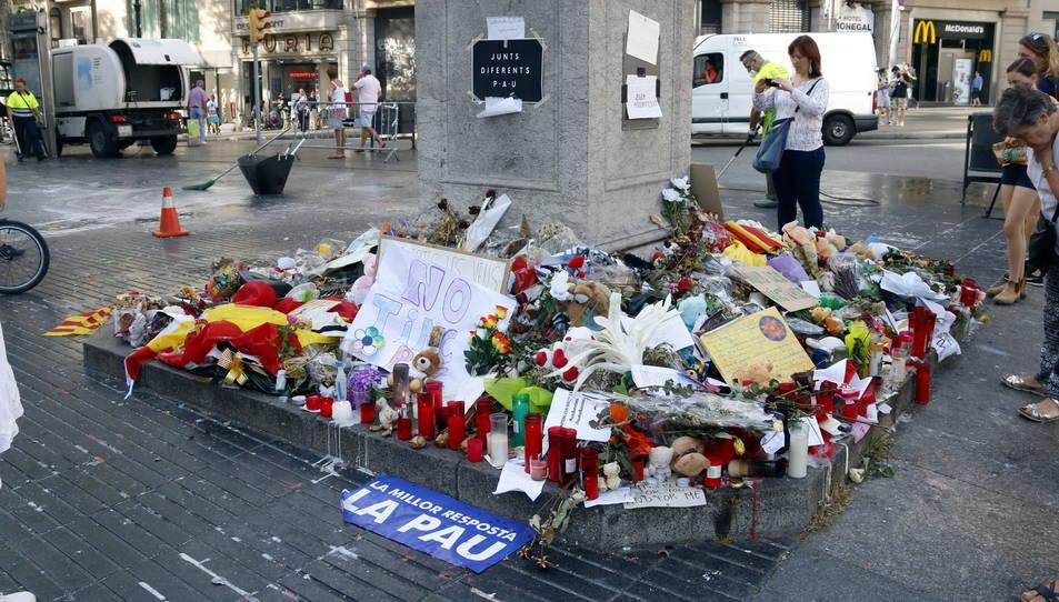 El pedestal de la columna del capdamunt de la Rambla amb flors i cartells de record.