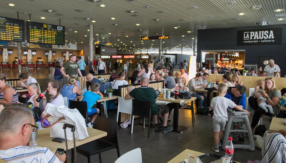 Passatgers a l'interior de la terminal esperen la sortida del seu avió, en una imatge d'arxiu.