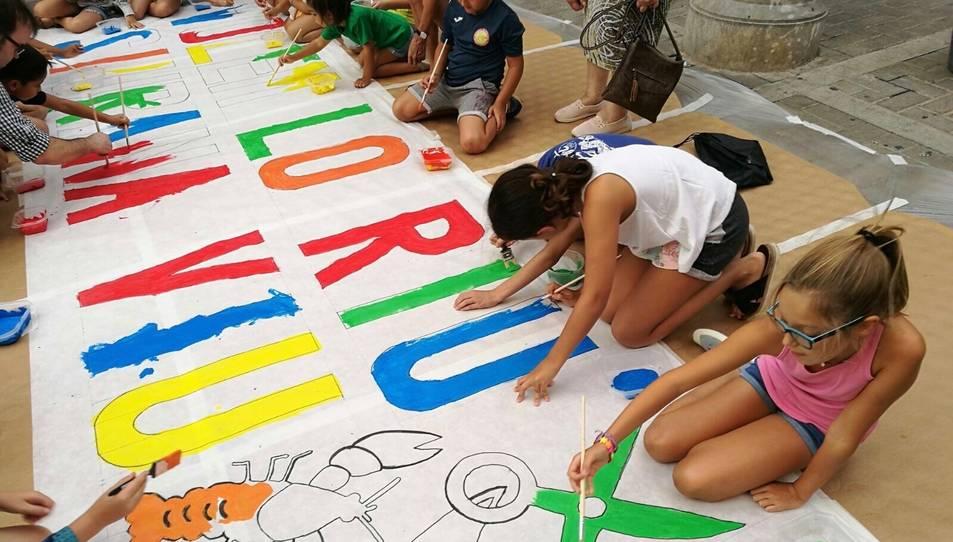 La pancarta que van pintar els nens es penjarà en un dels carrers del poble.