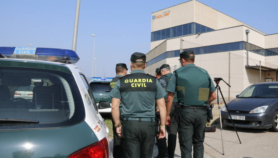 Agents de la Guàrdia Civil, d'esquena, davant les portes de les instal·lacions de la impremta de Constantí.