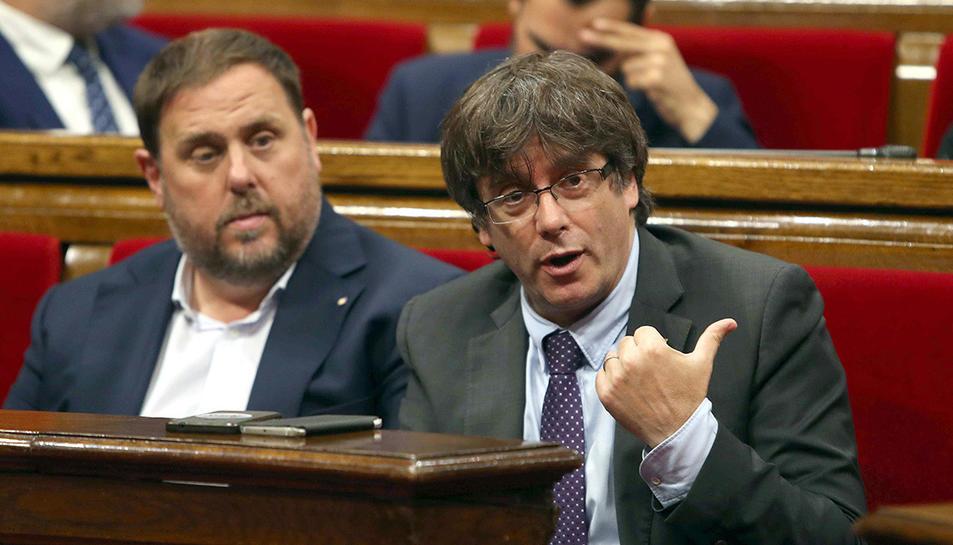 Carles Puigdemont i Oriol Junuers durant el debat parlamentari d'aquest dijous.