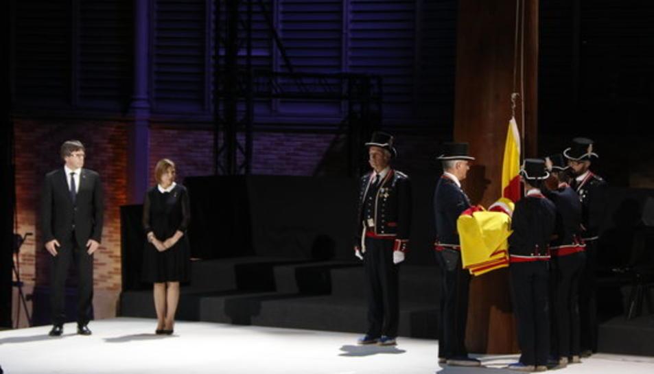 Puigdemont i Forcadell observen els Mossos vestits de gala apunt d'hissar la senyera a l'acte de la Diada celebrat al Born, el 10 de setembre de 2017.