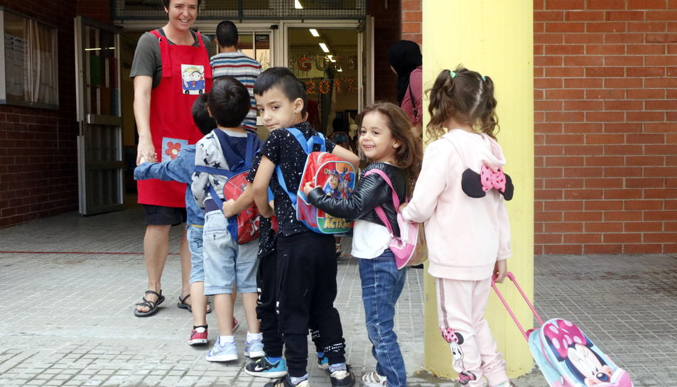 Pla obert d'un grup d'alumnes de l'institut-escola Mediterrani de Tarragona entrant en fila al centre amb la seva mestra. Imatge del 12 de setembre del 2017