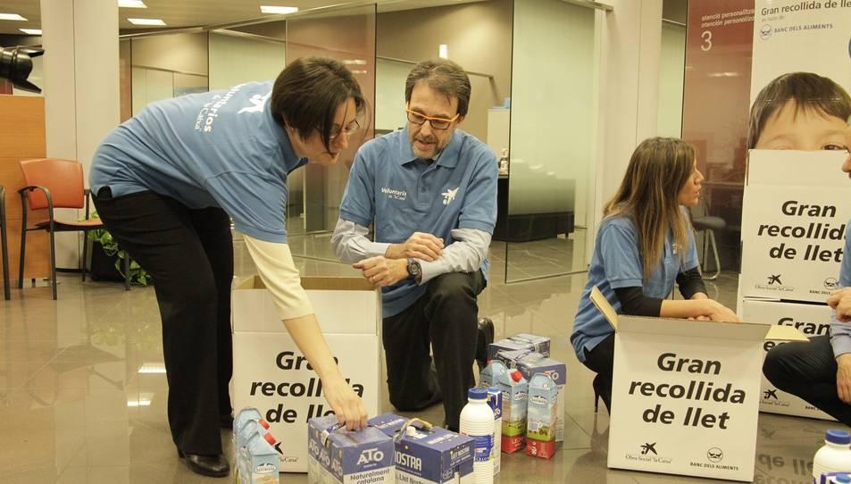 Voluntaris recollint la llet proporcionada per ciutadans durant la campanya.