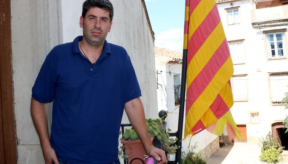 Pla mig de Xavier Gràcia, alcalde de Gratallops, al balcó de l'ajuntament amb la senyera al costat. Imatge del 14 de setembre de 2017 (horitzontal)
