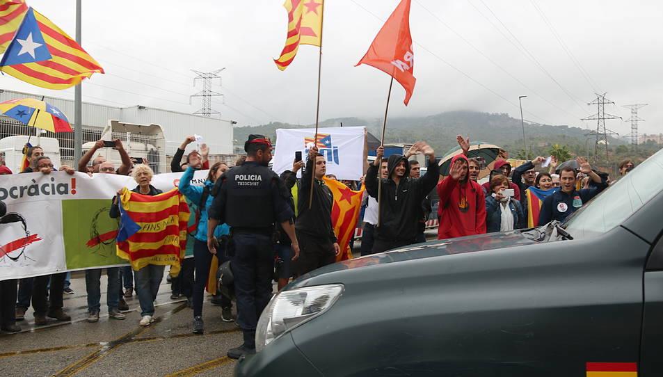 Un vehicle de la Guàrdia Civil marxant de la impremta de Sant Feliu de Llobregat mentre manifestants independentistes exhibeixen estelades i els diuen adéu amb la mà.