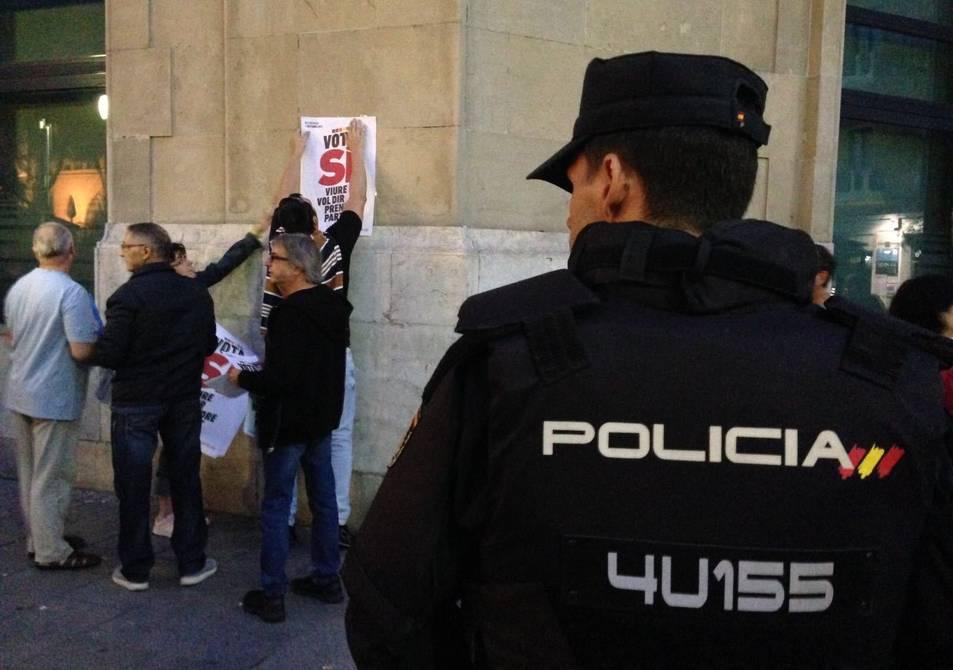 Un agent de la Policia contempla com manifestants a favor del referèndum enganxen un cartell.
