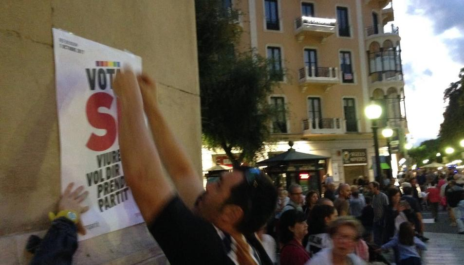 Un participant a l'enganxada col·locant un dels cartells favorables al Sí.