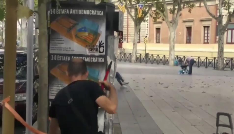 Instant del vídeo en què es mostra com diversos membres de Recortes Cero pengen cartells al Vendrell contra el referèndum.