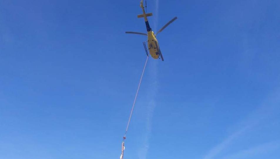 L'helicòpter realitzant els treballs a la línia elèctrica de difícil accés.