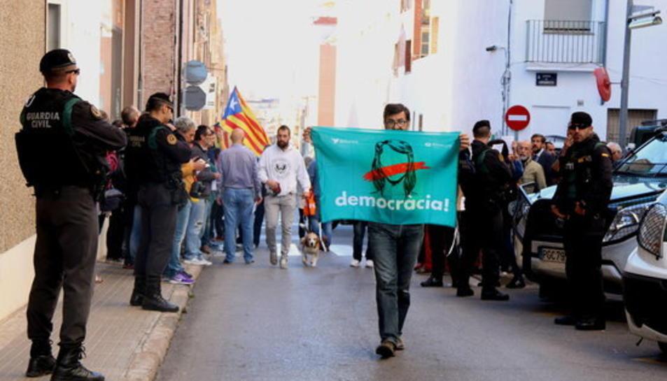 Un home amb la pancarta 'democràcia' d'Òmnium Cultural durant el registre de la Guàrdia Civil a l'empresa Unipost de Terrassa.
