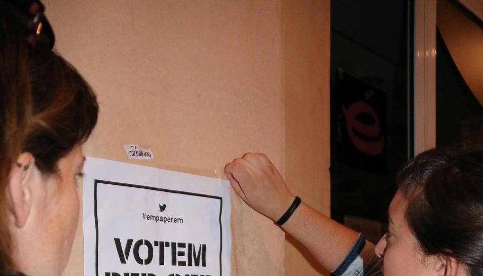 Dos persones enganxant un cartell en una façana de Tortosa, aquest 20 de setembre de 2017