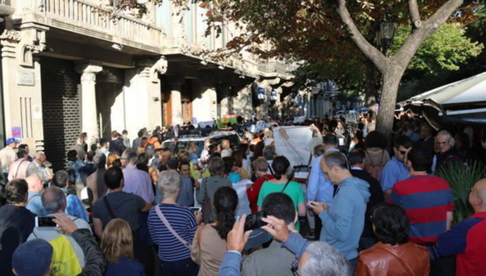 Pla general de la gent concentrada davant el Departament d'Economia i Finances amb la Guàrdia Civil al fons.