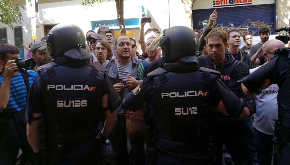 La policia espanyola envoltant la seu de la CUP, mentre simpatitzants criden en contra de l'actuació i en favor de l'1-O.