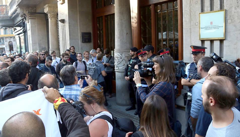 El portal del Departament d'Economia i Finances, a la Rambla de Catalunya de Barcelona, custodiat per Mossos i Guàrdia Civil, ple de periodistes i ciutadans amb cartells de 'democràcia'
