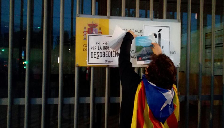Una manifestant posant un cartell anunciant el referèndum a la subdelegació del Govern a Tarragona.