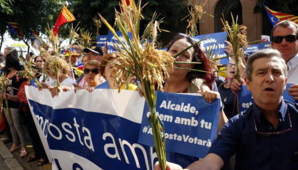 Un veí d'Amposta mostra una espiga d'arròs símbol del Delta mentre donen suport a l'alcalde.