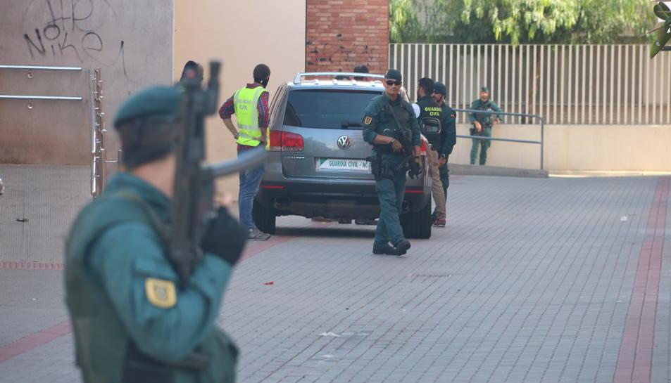 Imatge de diversos efectius de la Guàrdia Civil a Vinaròs, amb un agent amb arma llarga, desenfocat i en primer terme. Imatge del 22 de setembre del 2017