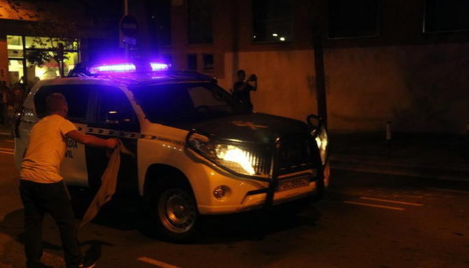 Imatge d'un cotxe de la Guàrdia Civil increpat per un manifestant i arribant a la Comandància de Guàrdia Civil de Travessera de Gràcia