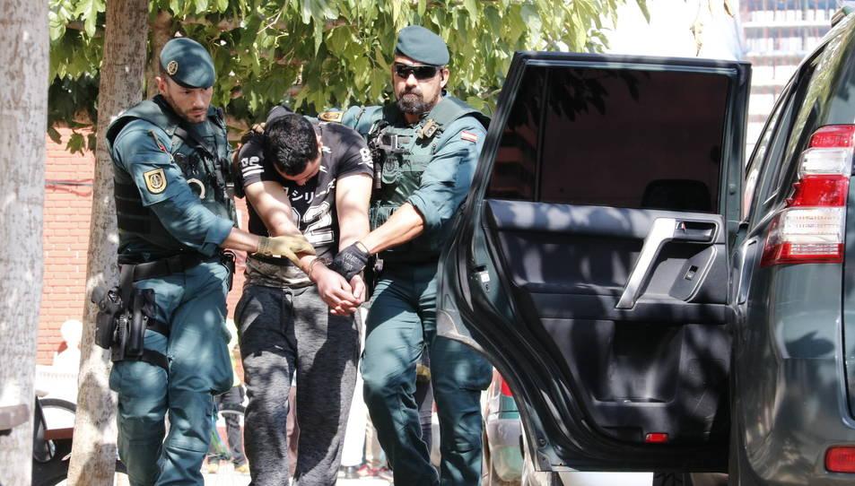 Imatge del noi detingut a Vinaròs, presumptament relacionat amb els atemptats de Barcelona i Cambrils, mentre el traslladen dos agents de la Guàrdia Civil al vehicle policial.