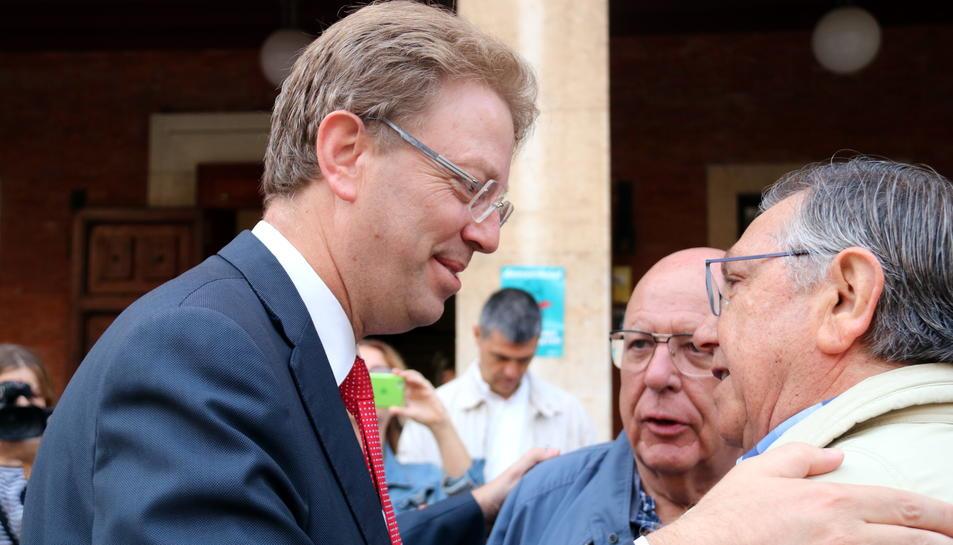 Primer pla de l'alcalde de Tortosa, Ferran Bel, abraçant-se a dos ciutadans a les portes de l'Ajuntament abans de marxar a Madrid per comparèixer davant del Fiscal. Imatge del 25 de setembre de 2017 (horitzontal)