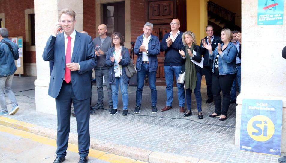 Pla general de l'alcalde de Tortosa, Ferran Bel, davant d'alguns regidors del consistori que aplaudeixen a les portes de l'Ajuntament per donar-li suport abans de la compareixença davant del Fiscal a Madrid. Imatge del 25 de setembre de 2017 (horitzontal)