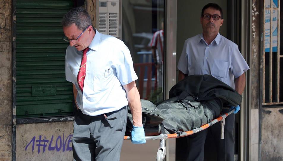 Empleats de la funerària retiren el cadàver de l'home.