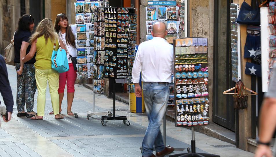 Unes turistes miren unes postals en una de les botigues de souvenirs del carrer Major.