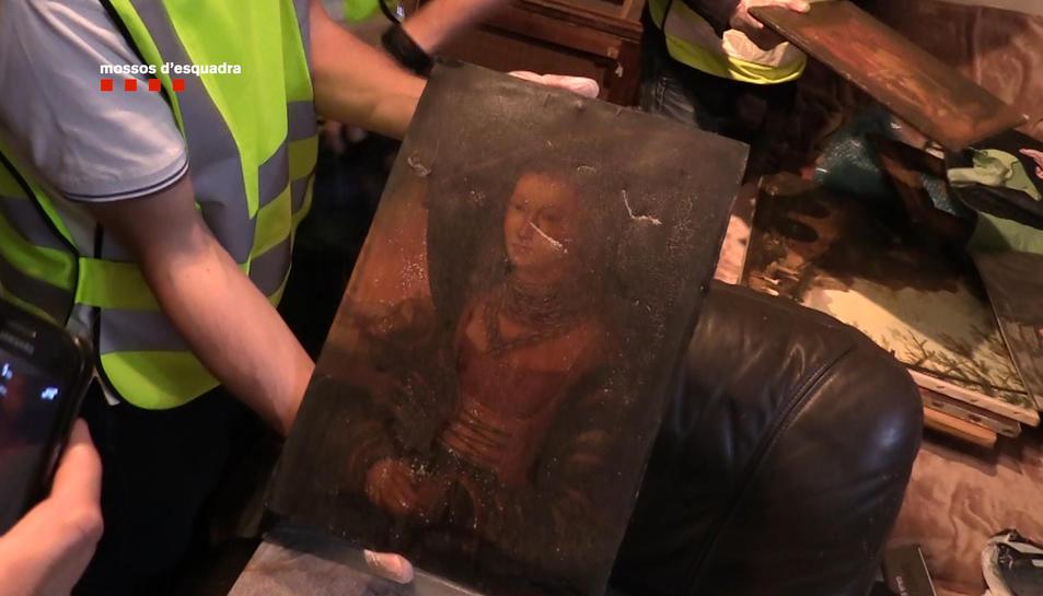 La policia intervenint una de les obres d'art robades pels detinguts.