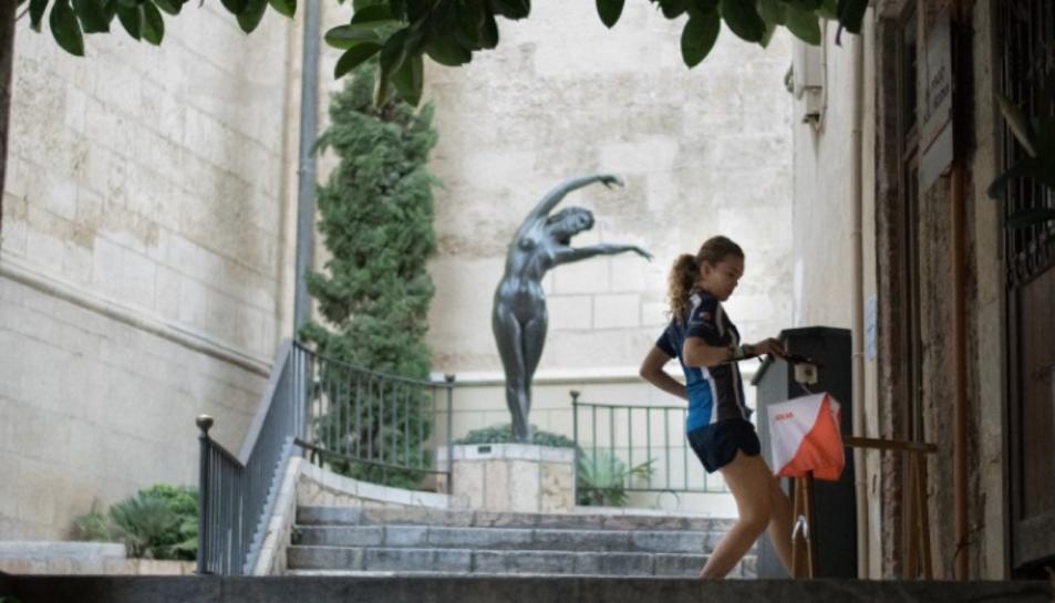 Noia practicant l'esport de l'orientació a la ciutat.