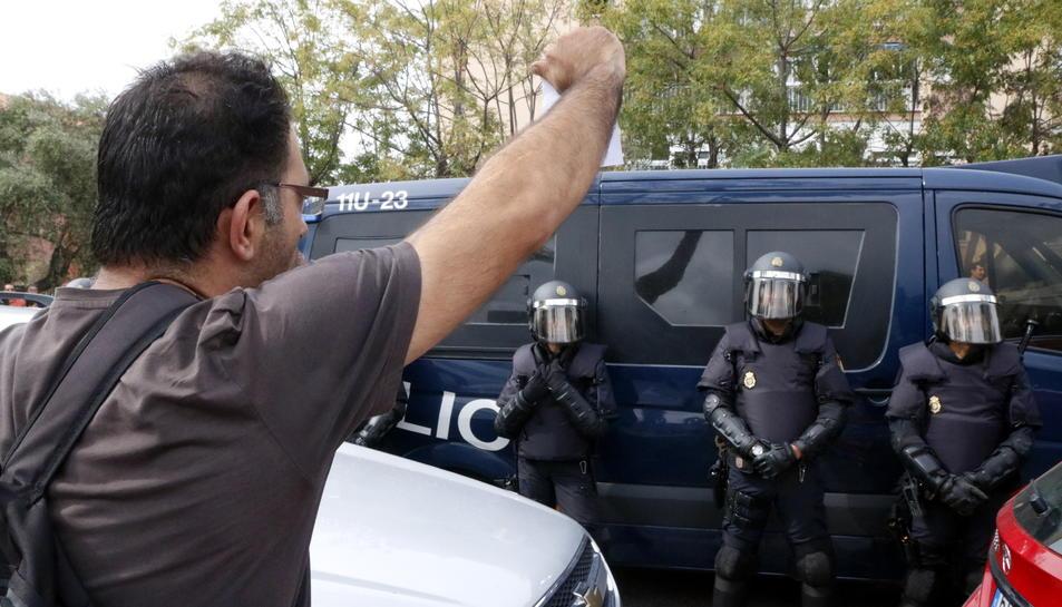 Pla mig d'un veí de Sant Salvador exhibint una papereta als agents desplegats davant l'institut d'aquest barri de Tarragona, l'1 d'octubre del 2017