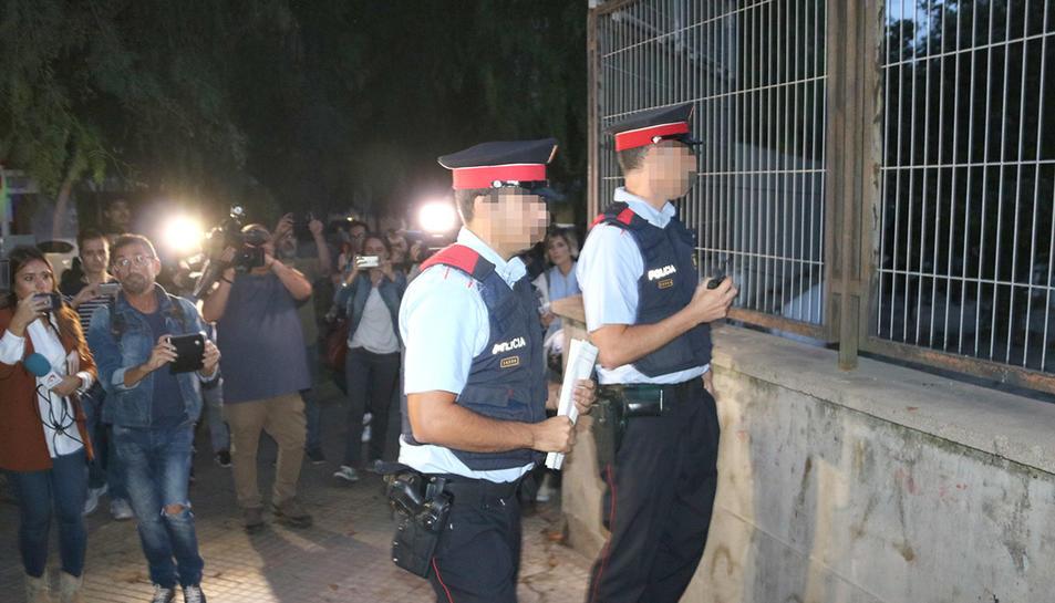 Dos agents dels Mossos que miren el recinte de l'institut Antoni Martí i Franquès de Tarragona.