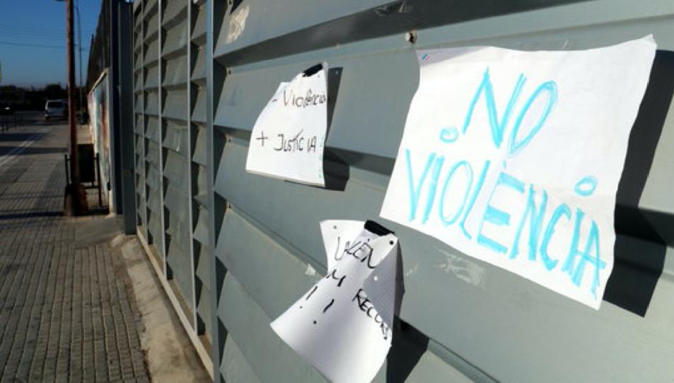 Primer pla de papers amb lemes contra la violència policial apegats a l'entrada de l'IES Joaquim Bau de Tortosa amb l'entrada buida d'alumnes a primera hora d'aquest dimarts, per l'Aturada de País
