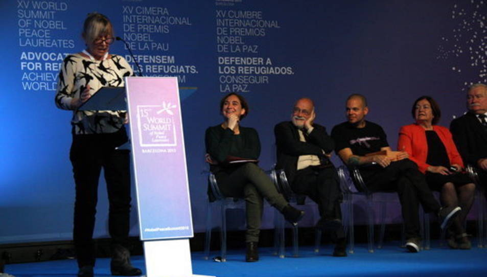 Jody Williams llegint la declaració dels Nobels de la Pau a Barcelona, mentre l'escolten Ada Colau, Aracadi Oliveres, René Pérez i Lech Walesa , el 15 de novembre de 2015 (horitzontal)