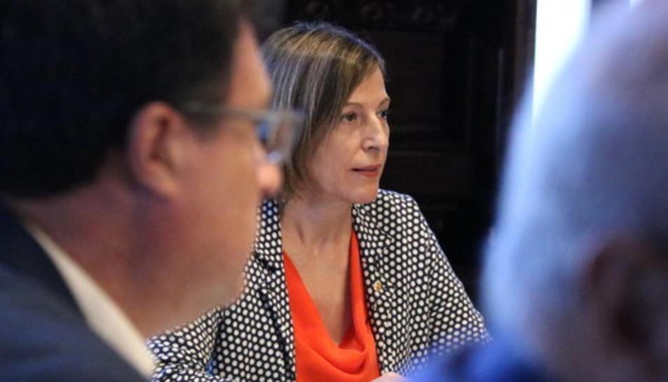 La presidenta del Parlament, Carme Forcadell, darrere del diputat de CSQP Joan Josep Nuet a la Mesa, el 10 d'octubre de 2017.