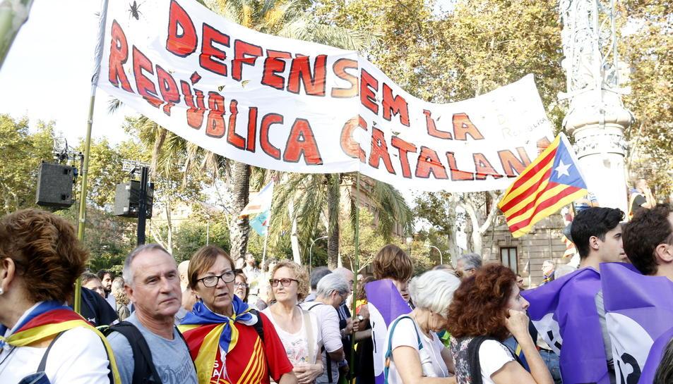 Persones concentrades al passeig de Lluís Companys per seguir la compareixença del president de la Generalitat.