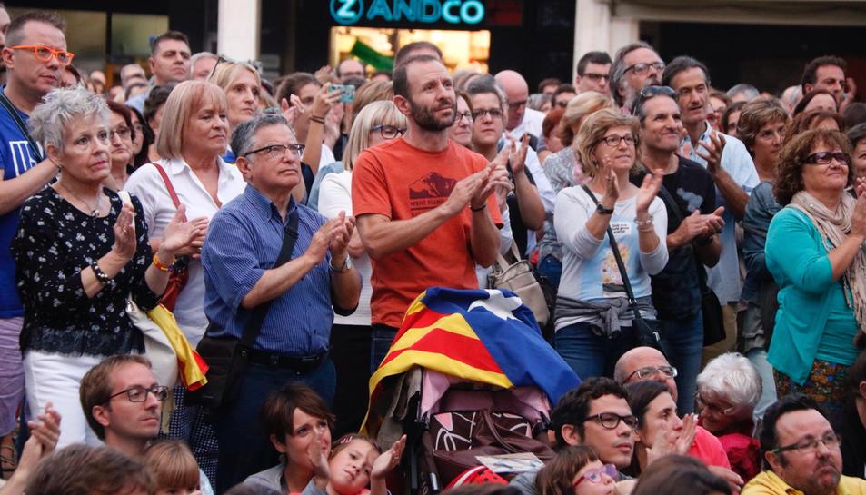 Ciutadans aplaudint a la plaça del Mercadal mentre seguien en directe la compareixença.