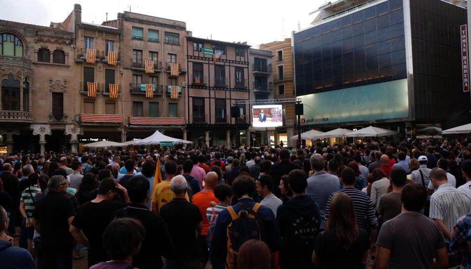 Els ciutadans omplint la plaça del Mercadal de Reus seguint la compareixença en una pantalla gegant.